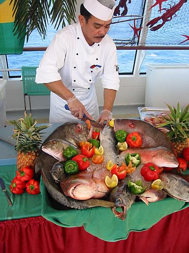 Koch auf der AIDAaura bereitet einen Fisch vor
