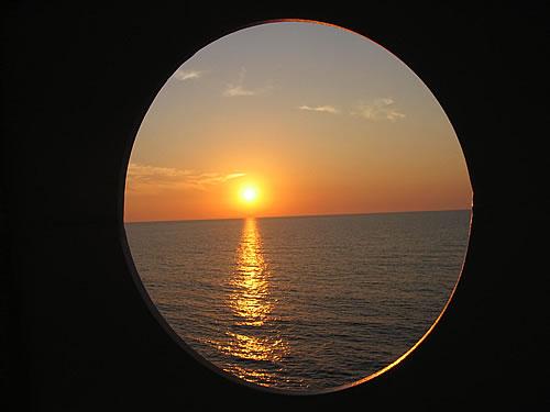 Blick durch ein Bullauge der AIDA auf den Sonnenuntergang
