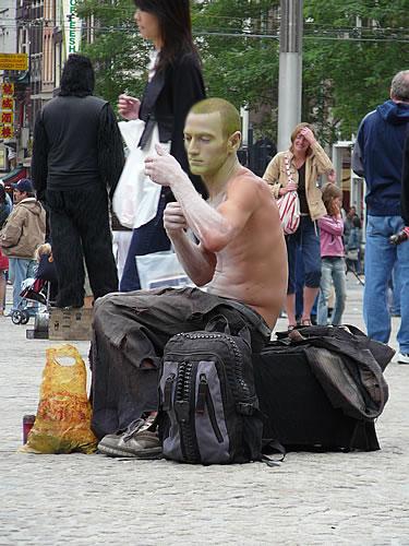 """Straßenkünstler, der auf dem """"Dam"""" sitzt und sich für seine Show vorbereitet"""